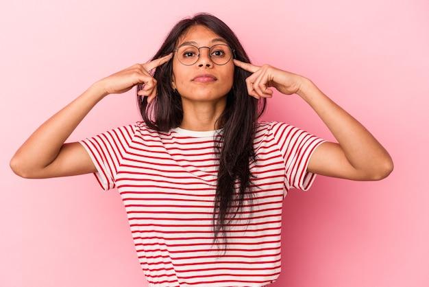 ピンクの背景に分離された若いラテン女性は、人差し指を頭に向けたまま、タスクに焦点を当てました。