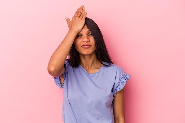 ピンクの背景に孤立した若いラテン女性は、何かを忘れて、手のひらで額を叩き、目を閉じます。