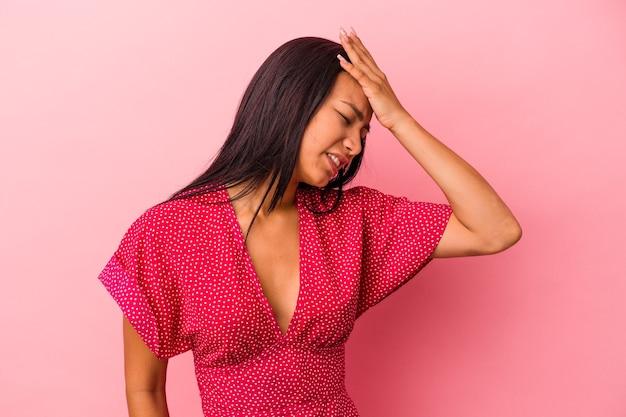 Молодая латинская женщина изолирована на розовом фоне, что-то забывая, хлопая ладонью по лбу и закрывая глаза.