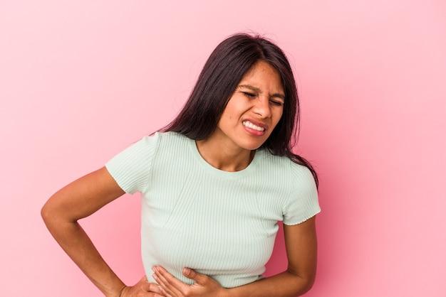 肝臓の痛み、胃の痛みを持っているピンクの背景に分離された若いラテン女性。