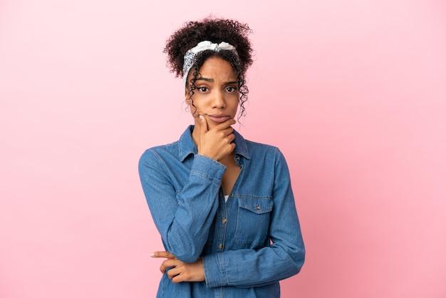 Молодая латинская женщина изолирована на розовом фоне с сомнениями