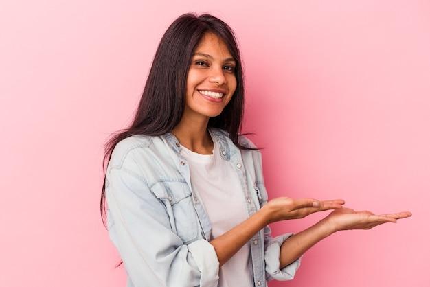 Молодая латинская женщина, изолированные на розовом фоне, держа копию пространства на ладони.