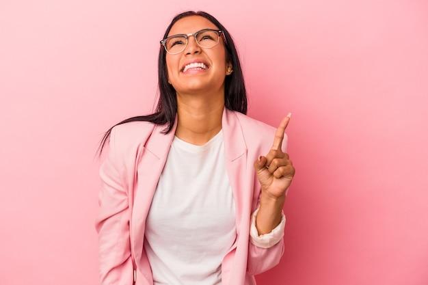 분홍색 배경에 고립된 젊은 라틴 여성은 두 앞 손가락으로 빈 공간을 표시함을 나타냅니다.
