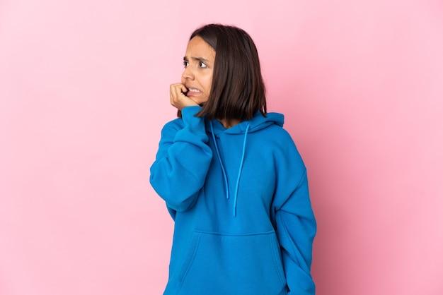 분홍색 배경에 고립 된 젊은 라틴 여자는 조금 긴장
