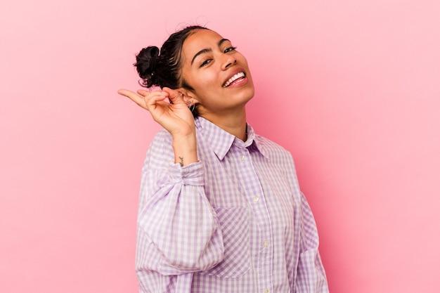 ピンクの背景にうれしくて屈託のない若いラテン女性が指で平和のシンボルを示しています。