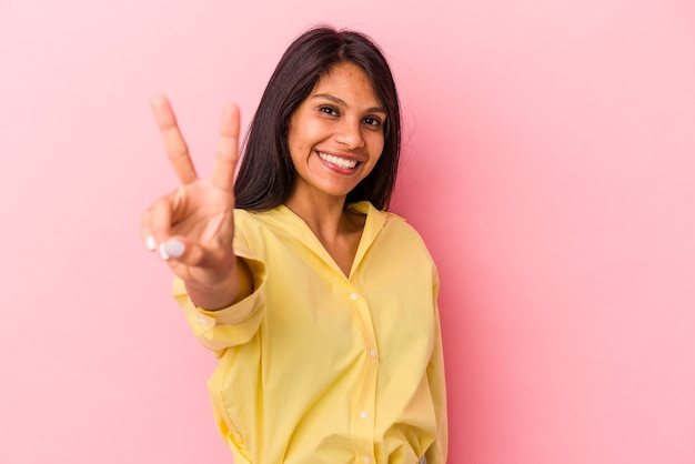 ピンクの背景に分離された若いラテン女性は、指で平和のシンボルを示して楽しくてのんき。