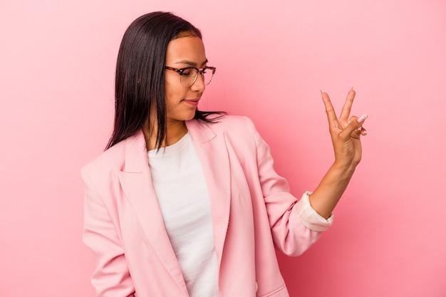 ピンクの背景に分離された若いラテン女性は、指で平和のシンボルを示して楽しくてのんきです。