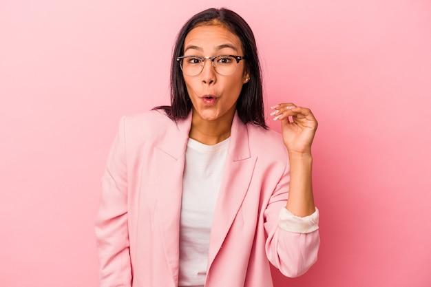 ピンクの背景に孤立した若いラテン女性は、手で口を覆って、何かについて笑っています。