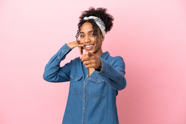 Молодая латинская женщина изолирована на розовом фоне, делая жест телефона и указывая вперед