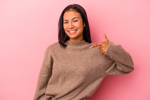 誇りと自信を持って、シャツのコピースペースを手で指しているピンクの背景の人に分離された若いラテン女性