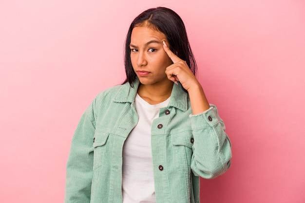 ピンクの背景に指で寺院を指して、考えて、タスクに焦点を当てて孤立した若いラテン女性。
