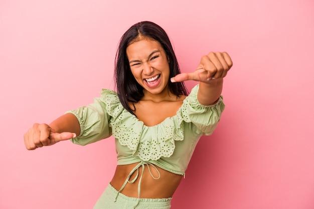 ピンクの背景に孤立した若いラテン女性は、両方の親指を上げて、笑顔で自信を持っています。