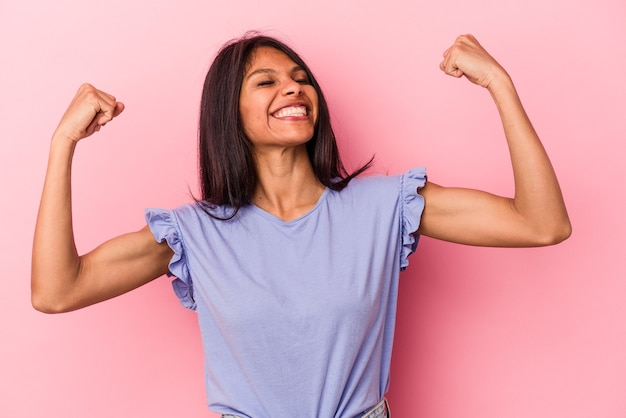 勝利、勝者の概念の後に拳を上げるピンクの背景に分離された若いラテン女性。