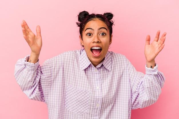 ピンクの背景に孤立した若いラテン女性が、うれしい驚きを受け、興奮して手を上げている。