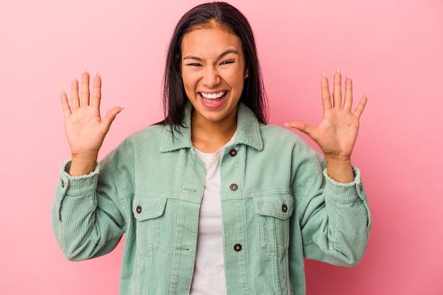 ピンクの背景に孤立した若いラテン女性は、嬉しい驚きを受け取り、興奮し、手を上げます。