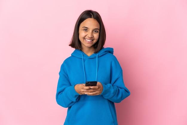 Молодая латинская женщина изолирована на розовом фоне, отправляя сообщение с мобильного телефона