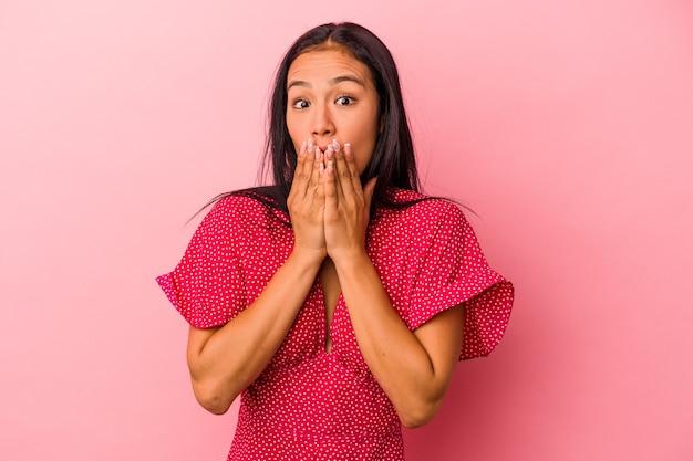 ピンクの背景に分離された若いラテン女性は、手で口を覆ってショックを受けました。
