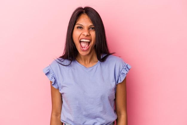 非常に怒っている、怒りの概念、欲求不満を叫んでピンクの背景に分離された若いラテン女性。