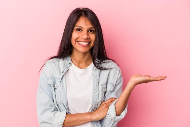 ピンクの背景に分離された若いラテン女性は、手のひらにコピースペースを示し、腰に別の手を保持しています。