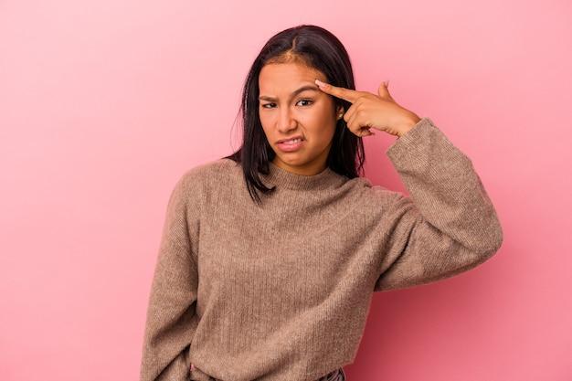 人差し指で失望のジェスチャーを示すピンクの背景に分離された若いラテン女性。