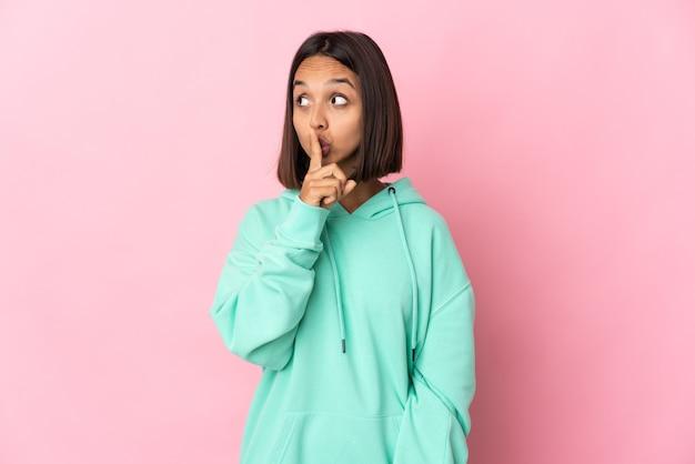 口に指を置く沈黙ジェスチャーの兆候を示すピンクの背景に分離
