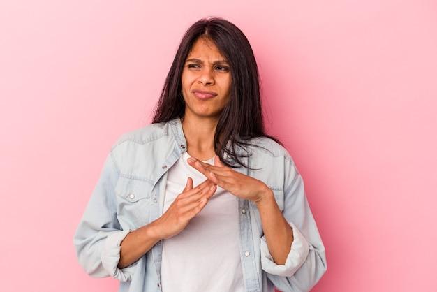 タイムアウトジェスチャーを示すピンクの背景に分離された若いラテン女性。