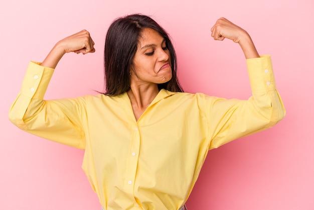 Молодая латинская женщина изолирована на розовом фоне, показывая жест силы руками, символ женской силы