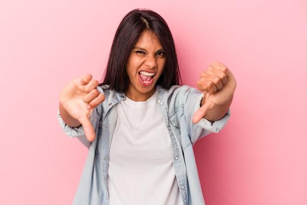 親指を下に示し、嫌悪感を表現するピンクの背景に分離された若いラテン女性。