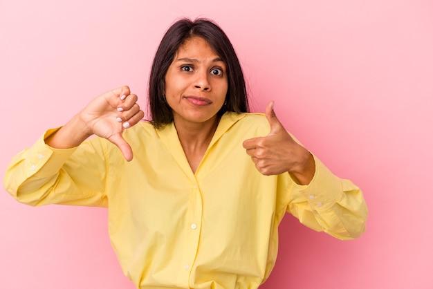 親指を上と親指を下に示すピンクの背景に分離された若いラテン女性、難しい選択の概念