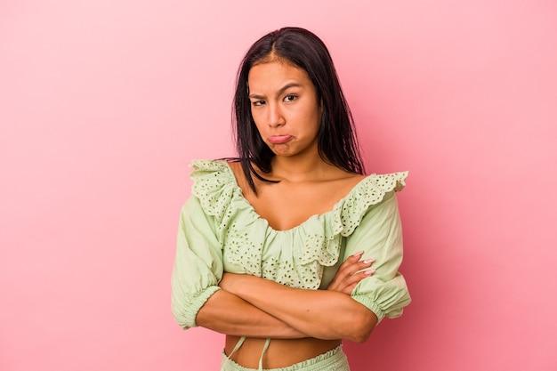 ピンクの背景に分離された若いラテン女性は肩をすくめると混乱した目を開いています。
