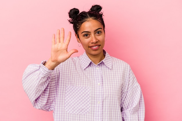 指で 5 番を示す陽気な笑顔のピンクの背景に分離された若いラテン女性。