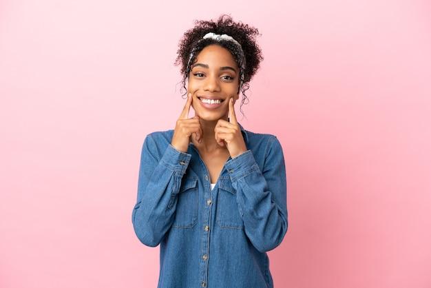 Молодая латинская женщина изолирована на розовом фоне, улыбаясь счастливым и приятным выражением лица