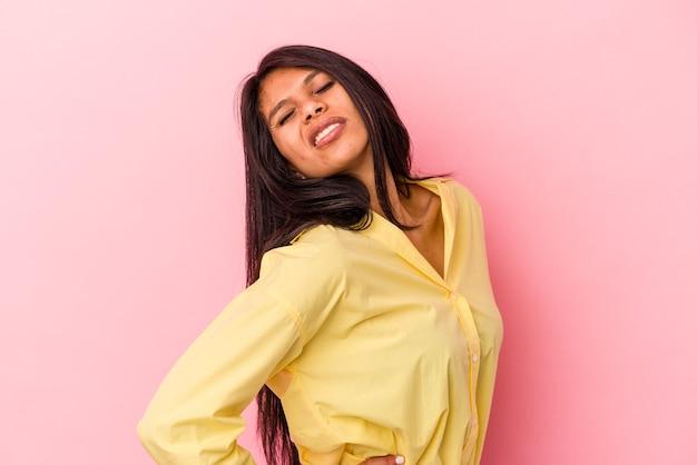 背中の痛みに苦しんでピンクの背景に分離された若いラテン女性。