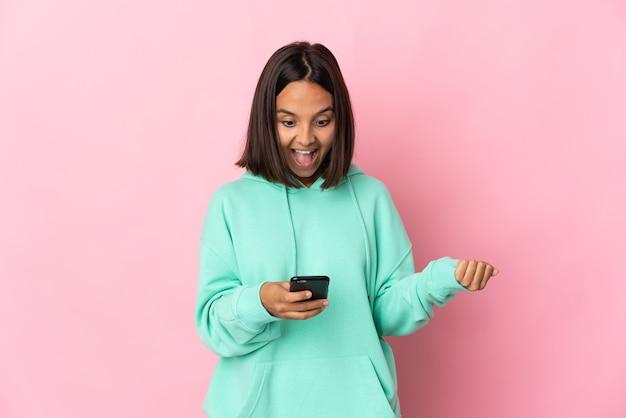 놀란 분홍색 배경에 고립 된 젊은 라틴 여자와 메시지를 보내는