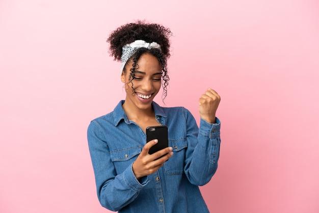 ピンクの背景に分離された若いラテン女性は驚いてメッセージを送信します
