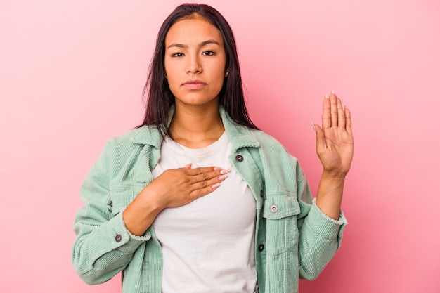 胸に手を置いて、誓いを立ててピンクの背景に分離された若いラテン女性。