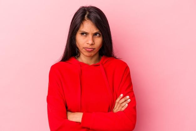 분홍색 배경에 격리된 젊은 라틴 여성은 반복적인 작업에 지쳤습니다.