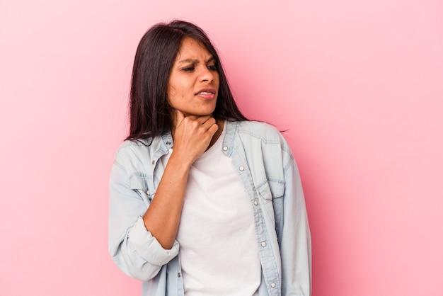 분홍색 배경에 고립된 젊은 라틴 여성은 머리 뒤쪽을 만지고 생각하고 선택합니다.