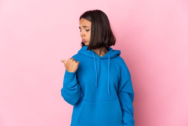Молодая латинская женщина изолирована на розовом фоне несчастной и указывая в сторону