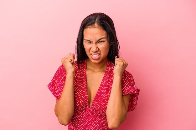 ピンクの背景に分離された若いラテン女性は緊張した手で叫んで動揺します。