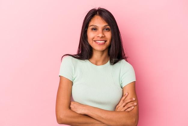自信を持って、決意を持って腕を組んで、ピンクの背景に孤立した若いラテン女性。 Premium写真
