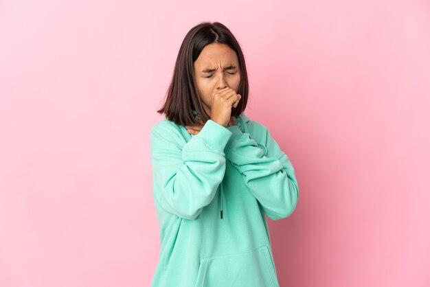 많은 기침 분홍색 벽에 고립 된 젊은 라틴 여자