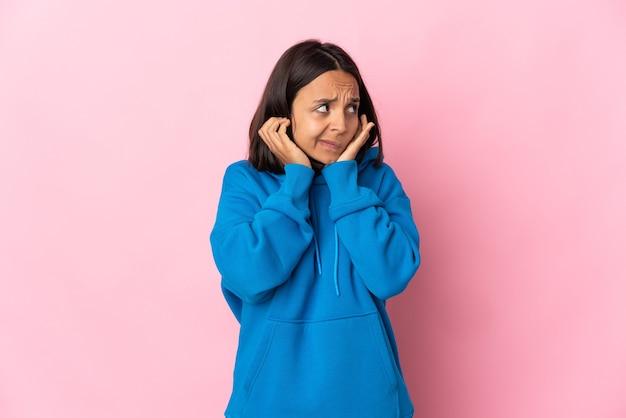 欲求不満と耳を覆っているピンクの壁に孤立した若いラテン女性