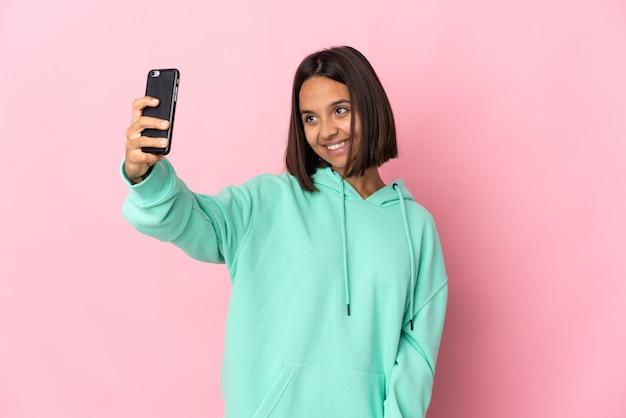 Молодая латинская женщина изолирована на розовой стене, делая селфи