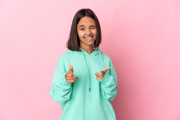 正面を指して笑顔のピンクの壁に分離された若いラテン女性