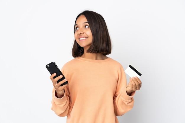 Молодая латинская женщина изолирована на белом фоне, покупая с мобильного с помощью кредитной карты, думая