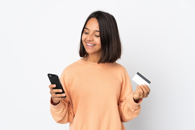 Молодая латинская женщина, изолированные на белом фоне, покупает с мобильного с помощью кредитной карты