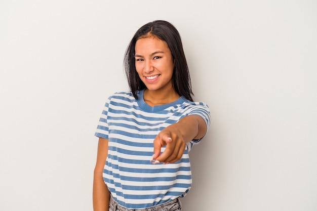 Молодая латинская женщина, изолированных на белом фоне, веселые улыбки, указывая на фронт.