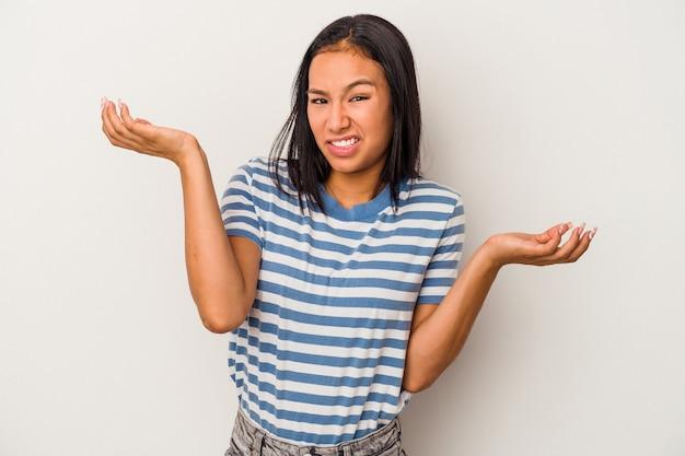 흰색 배경에 격리된 젊은 라틴 여성은 복사 공간을 유지하기 위해 혼란스럽고 의심스러운 어깨를 으쓱하고 있습니다.