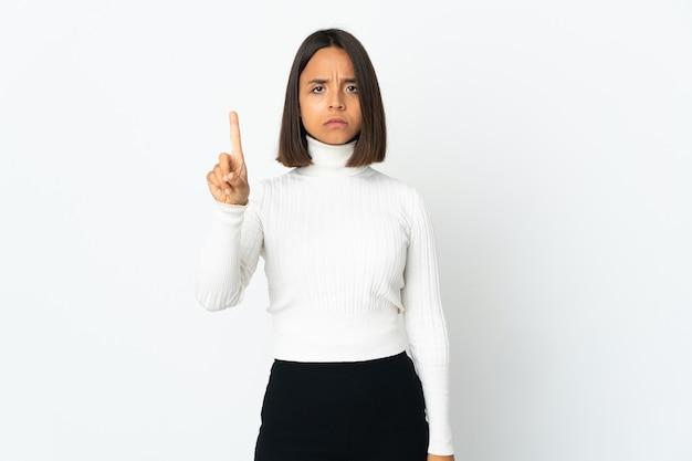 심각한 표정으로 하나를 세는 흰색 배경에 고립 된 젊은 라틴 여자